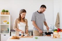 Keuken van het paar de kokende voedsel thuis stock afbeeldingen