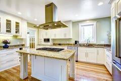 Keukeneiland met ingebouwd fornuis, granietbovenkant en kap Stock Afbeelding