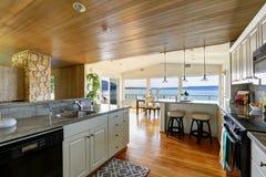 Keukengebied met met panelen beklede plafond en hardhoutvloer Stock Fotografie