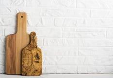 Keukengereedschap, olijf scherpe raad op een keukenplank tegen een witte bakstenen muur Selectieve nadruk royalty-vrije stock afbeelding