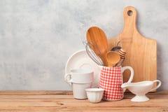 Keukengerei en vaatwerk op houten lijst over rustieke achtergrond Royalty-vrije Stock Foto