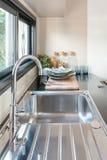 Keukengootsteen met tapkraan op zwarte teller Stock Afbeeldingen