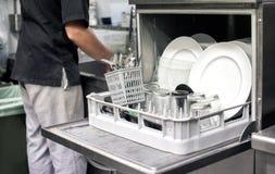 Keukenhand met een open afwasmachine Stock Afbeelding