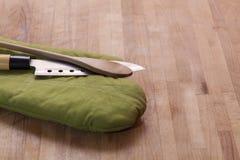 Keukenhandschoen met mes en lepel op houten raad Royalty-vrije Stock Foto's