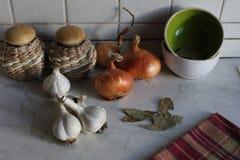 Keukenhoek met witte knoflookkruidnagels, gouden uien, potten en theedoek royalty-vrije stock afbeelding