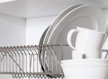 Keukenkast met een rooster voor schotels, met een witte en zwarte plaat, koppen stock fotografie