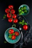 Keukenlijst met verse tomaten, basilicum en zout en peper met vork en servet wordt verfraaid dat Royalty-vrije Stock Foto