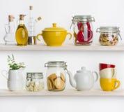 Keukenplanken met diverse voedselingrediënten en werktuigen op wit Royalty-vrije Stock Fotografie