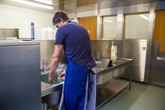 Keukenportier het wassen omhoog bij gootsteen Stock Foto's