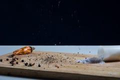 Keukenraad met peper en verspreid zout Stock Foto's