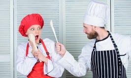 Keukenregels Culinair slagconcept De culinaire vrouw en de gebaarde man tonen concurrenten Who betere kok uiteindelijk royalty-vrije stock foto's