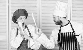 Keukenregels Culinair slagconcept De culinaire vrouw en de gebaarde man tonen concurrenten Who betere kok uiteindelijk royalty-vrije stock fotografie