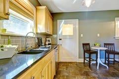 Keukenruimte met de kabinetten van de esdoornopslag en het dineren gebied Stock Afbeeldingen