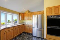 Keukenruimte met granietbovenkanten en zwarte tegelvloer Stock Fotografie