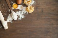 Keukensamenstelling met fettuccine gebarsten eieren, keukengerei, bloem Stock Afbeelding