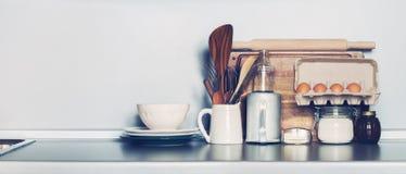 Keukenschotels, Tafelgerei, Kruidenierswinkel en Verschillend Materiaal op Tafelblad De ruimte van het exemplaar stock afbeeldingen