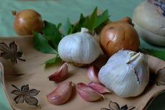 Keukenstilleven die uit groente en kruiden voor gezondheid bestaan - knoflook, ui, selderie en citroenbalsem Royalty-vrije Stock Fotografie