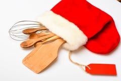 Keukentoebehoren of uitrusting van keukengerei in grote rode sok, witte achtergrond worden ingepakt die Het concept van het Kerst stock fotografie