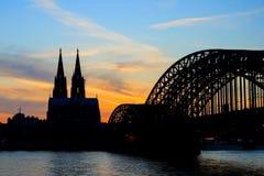 Keulen Koln Duitsland tijdens zonsondergang, de brug van Keulen met kathedraal stock afbeelding