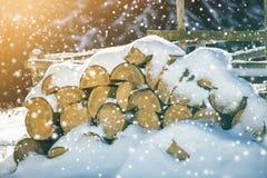 Keurig opgestapelde stapel van gehakt droog die boomstammenhout met sneeuw in openlucht op heldere koude de winter zonnige dag wo stock fotografie