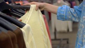Keus van de jasjes die van manierkleren op houten hangers bij opslagwinkel hangen Persoonshanden die kleren selecteren stock footage