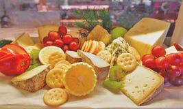 Keuzen van kaasverscheidenheid met vruchten en koekjes Stock Foto