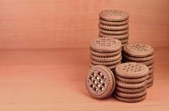 Kex för chokladsmörgåsrunda med vanilj lagar mat med grädde fyllning på den bruna trätabellen med copyspace Stilleben av sött och Royaltyfria Bilder