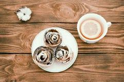 Kex med pudrat socker och varmt te med citronen royaltyfri bild