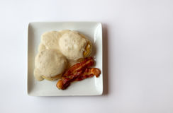 Kex och sky med två skivor av bacon på en isolerad platta Arkivfoto