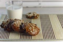 Kex på tabellen med sesamfrö, russin och ett exponeringsglas av mjölkar På fönster-fönsterbrädan äta som är sunt Arkivbilder