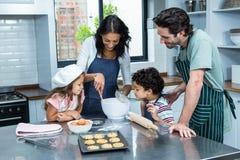 kexar som tillsammans lagar mat den lyckliga familjen Royaltyfri Bild