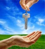 Key. Hand giving key on nature background Royalty Free Stock Image