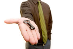 The key. Man giving an old key to you Stock Images