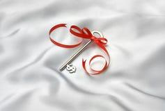 Key. With white satin cloth background Stock Photos