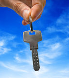 Key. In hand over blue sky Royalty Free Stock Photo