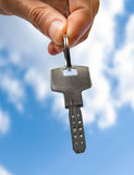 Key. In hand over blue sky Stock Photos