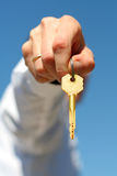 Key. Hand holds a gold key (key in focus Royalty Free Stock Photos