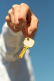 Key. Hand holds a gold key (key in focus Stock Images