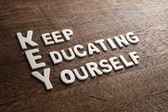 Key Acronym Keep Educating Yourself. Wood letters on wood texture royalty free stock photo