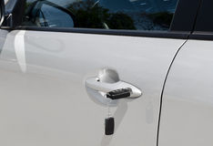 Key with alarm system in the car door Royalty Free Stock Photography