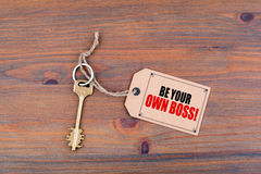 Free Key And A Note On A Wooden Table With Text - Be Your Own Boss Stock Photography - 81264342