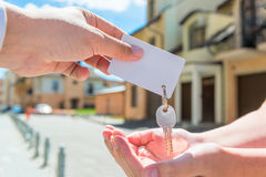 Key of apartment and a card in the hands Royalty Free Stock Image