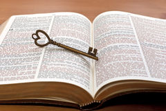 Key on the Bible page. Key on the open Bible, key to the Bible knowledge concept stock image