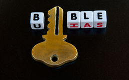 Key into the bible. Text ' bible ' in uppercase black letters on small white cubes with gold key replacing the letter ' i' on a dark background Stock Photo