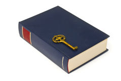 Key on book. Old brass key on blue book stock photos