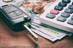 Key from the car and calculator on money. US currency Royalty Free Stock Photo