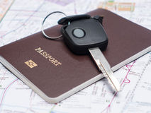 Key from the car and passport on map. Stock Photography