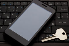 Key and  cell phone at the keyboard. Photo serie with Headphones and mobile phone at the keyboard background Royalty Free Stock Photos