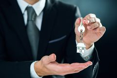 Key chain with key in hand of a real estate agent stock image