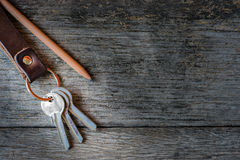 Key chain and pencil on wooden background. Stock Image